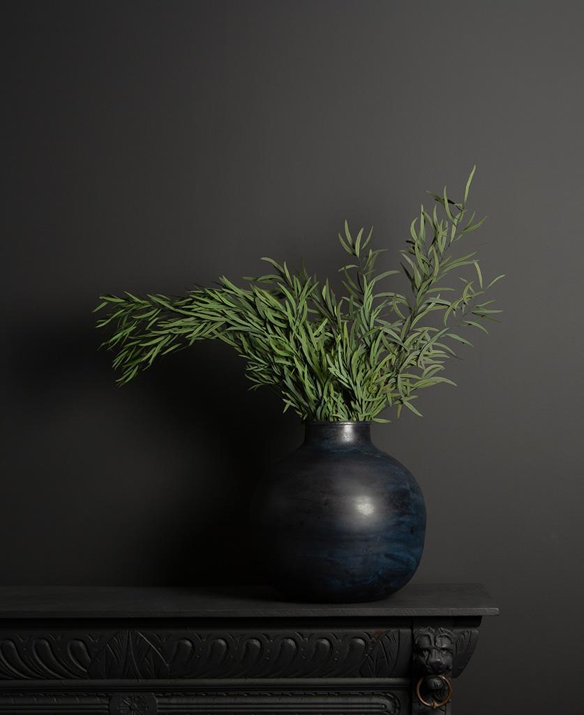 etnik vase with green eucalyptus nicholii bouquet on dark background
