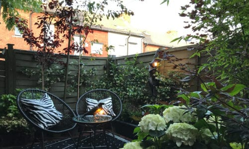 garden patio with two chairs and a table, a black raven table lamp and black monkey wall light
