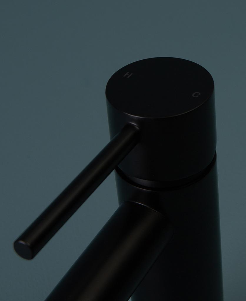 black inga tap close up of handle on blue background