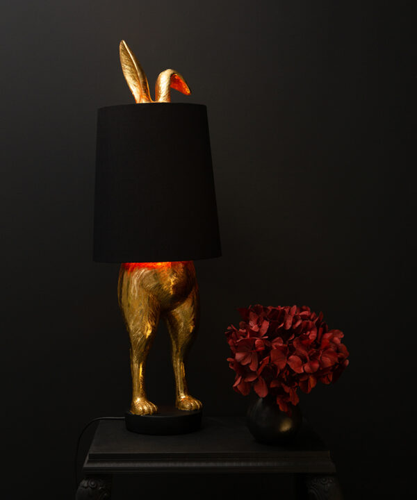 hiding bunny rabbit gold table lamp with black shade on black background