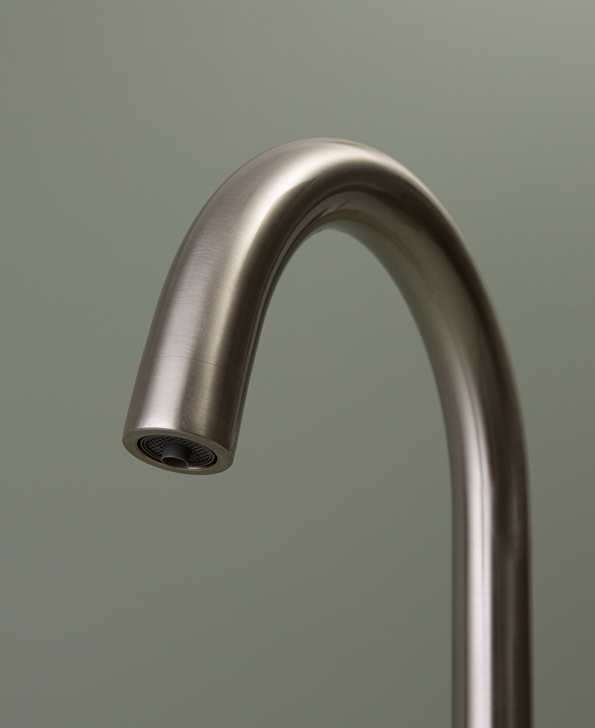 silver monroe hot water tap close up of spout on green background