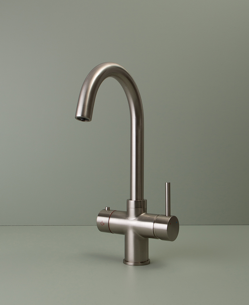 silver monroe hot water tap on green background