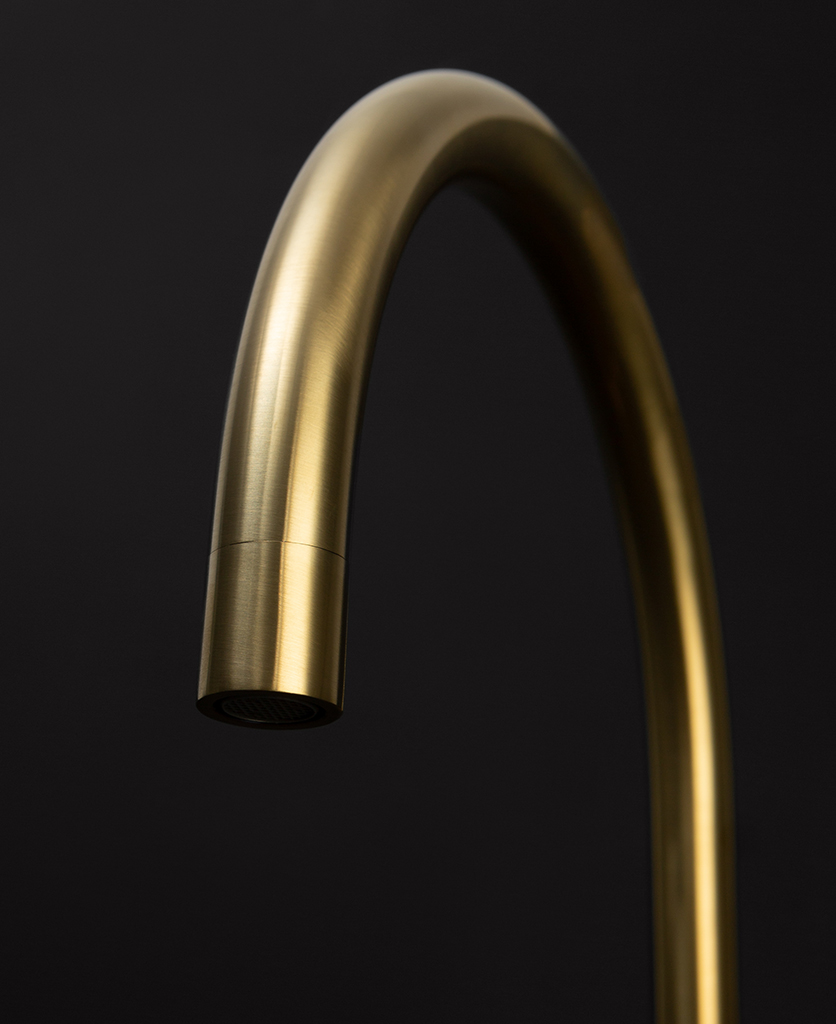 gold reeded tap close up of spout on black background