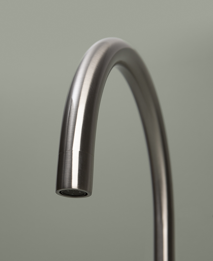 silver reeded tap close up of spout on grey background