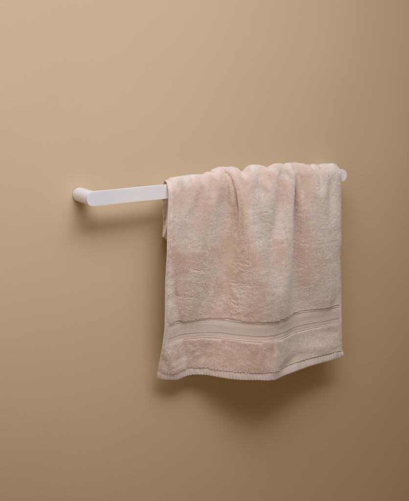 white towel rail on peach background