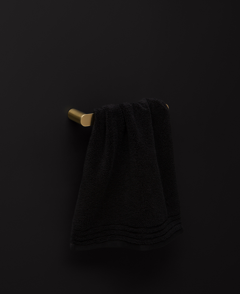 small gold towel rail on black background