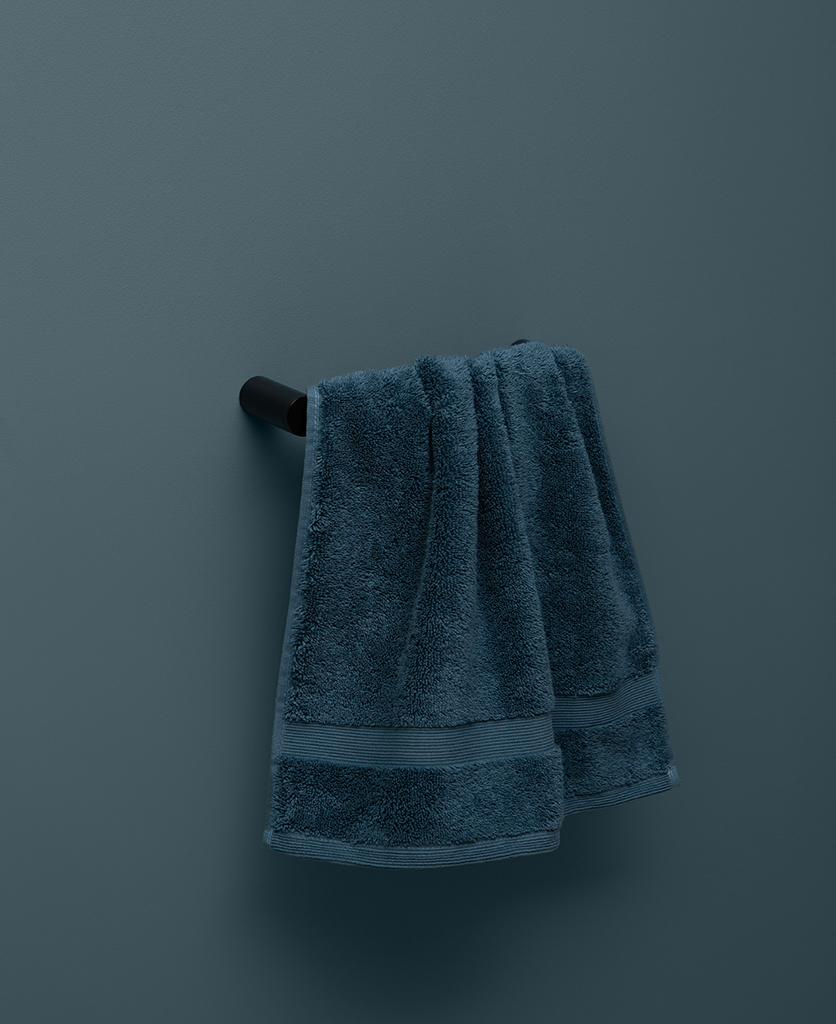 small black towel rail on blue background