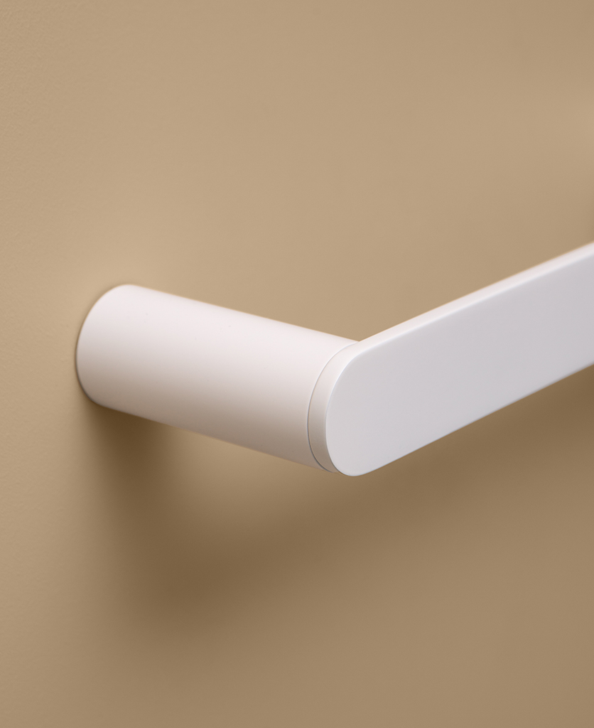 close up of white towel rail on peach background