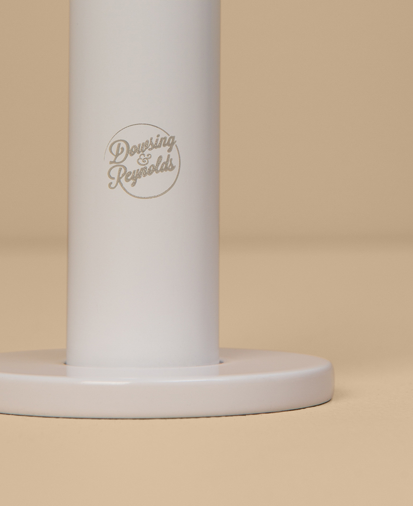 white reeded tap close up of logo on peach background
